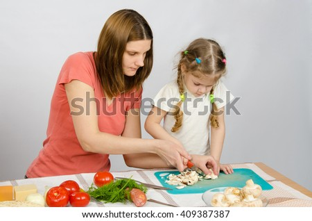 Mom shows daughter how to cut a small knife mushrooms