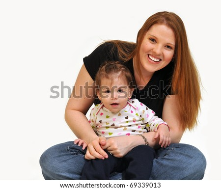 Mom sitting with daughter on her lap, looking at  camera, smiling over a white background. - stock photo