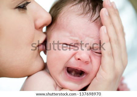 Mom soothes a crying baby - stock photo