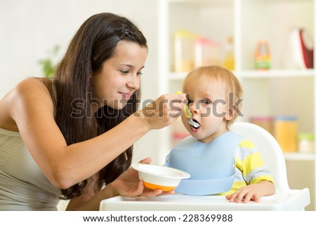 Mom spoon feeds baby child boy at home - stock photo