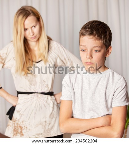 Mom swears by son. Conflict, problems in family. Sad mother and child - stock photo
