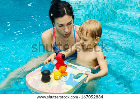 Mom teaches baby to swim in water - stock photo