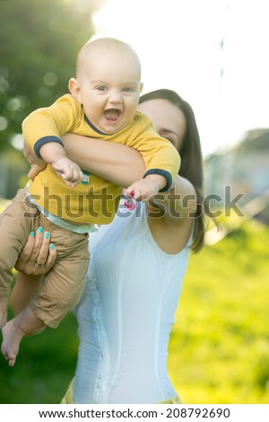 Mom throws baby in her arms up in the park - stock photo