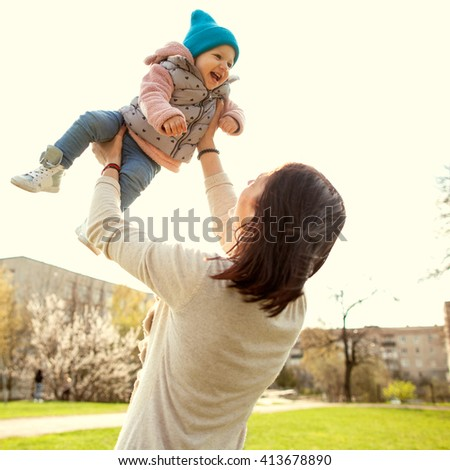 Mom throws baby in up above him, happy together, spring, Mother's Day