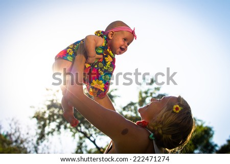 Mom throws up into the sky on the background of your child of the setting sun - stock photo