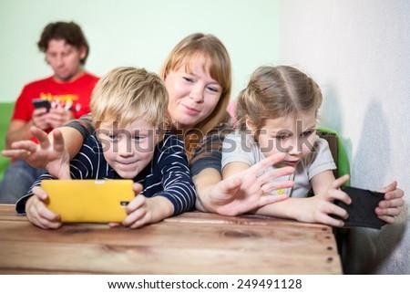 Mom trying to grab smartphones in children hands - stock photo