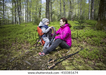 Mom walks in the forest with a child, a child in the children carry.
