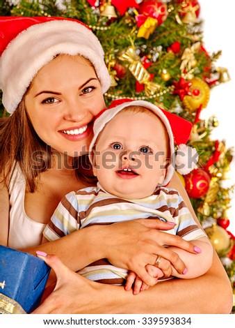 Mom wearing Santa hat gently hugs baby son  under Christmas tree. - stock photo