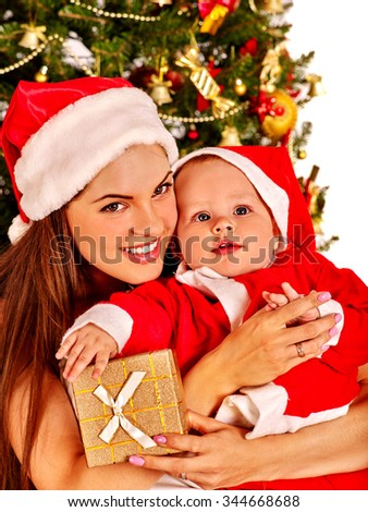 Mom wearing Santa hat holding  baby Santa with gold gift box  under Christmas tree. - stock photo