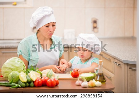 Mom with a child cooks in the kitchen