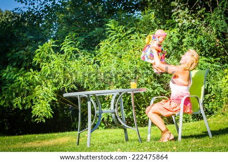 Mom with a small child sits at a table on a background of green lawn