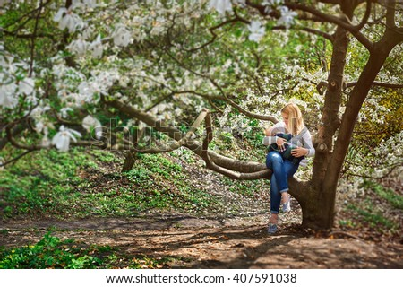 Mom with baby boy sitting on tree branch in the flowered spring garden