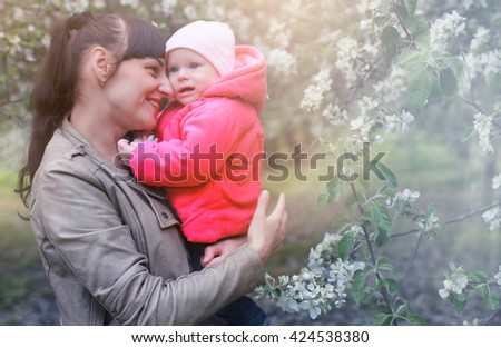 mom with baby in apple garden - stock photo