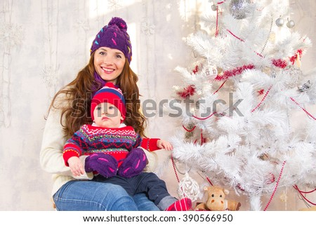 Mom with baby near Christmas tree - stock photo