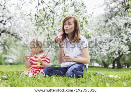 mom with beautiful daughter blowing soap bubbles - stock photo