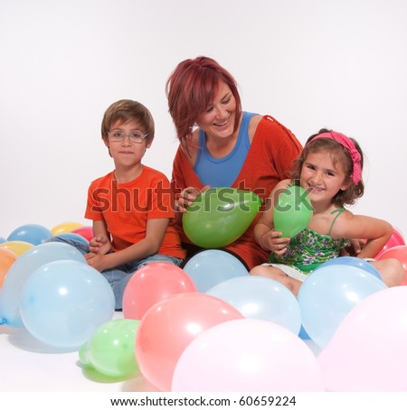 Mom with boy and girl playing with colourful balloons - stock photo