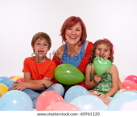 Mom with boy and girl playing with colourful balloons