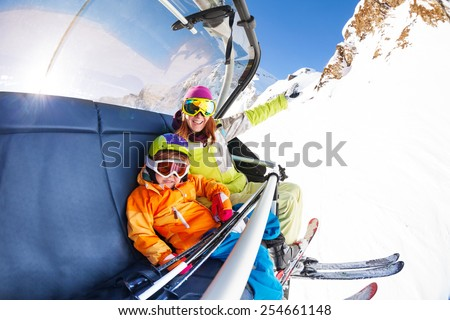 Mom with boy on ski lift ropeway chair  - stock photo