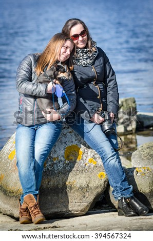 Mom with daughter and small dog relaxing on spring sea coast - stock photo
