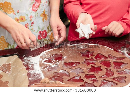 Mom with daughter cutting out the Christmas symbols in the dough for the cookies
