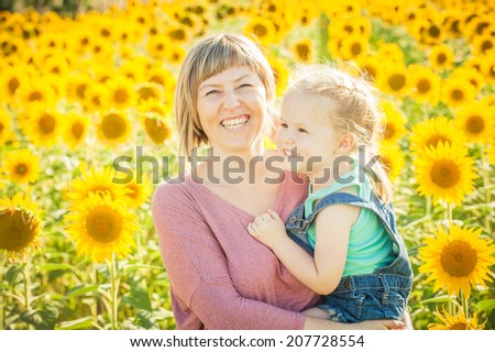 Mom with daughter in between beautiful sunflowers in summer day.