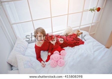 Mom with daughter in red dress lying on a big white bed - stock photo