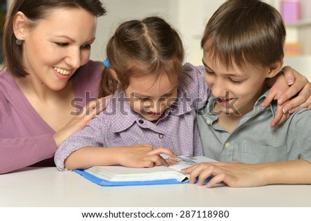 Mom with her children reading a book