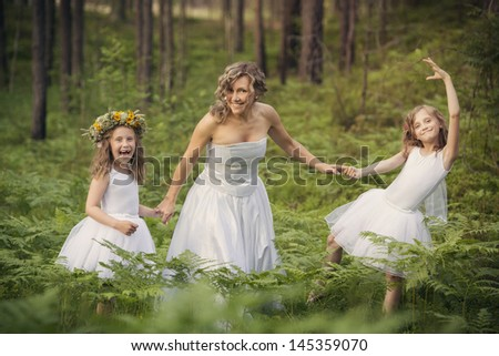 Mom with her daughters in the forest, all dressed in white ballerina dresses and happily dancing.