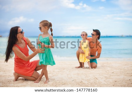 Mom with her older daughter in the foreground and dad with youngest daughter in the background on the beach - stock photo