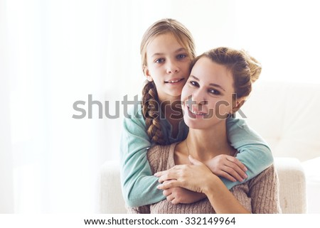Mom with her pre teen daughter hugging, positive feelings, good relations. - stock photo