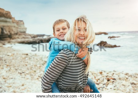 Mom with her son play on the sea shore. Child hugging mother.