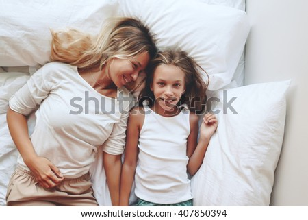 Mom with her tween daughter relaxing in bed, positive feelings, good relations. Top view.