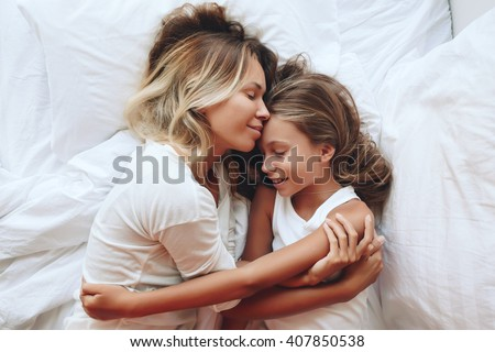 Mom with her tween daughter relaxing in bed, positive feelings, good relations. Top view. - stock photo
