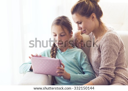Mom with her tween daughter using ipad together - stock photo