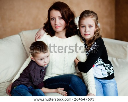 Mom with her two children sitting on the couch at home