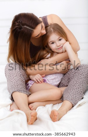 Mom with her 6 years old little daughter dressed in pajamas are relaxing and playing in the bed at the weekend together, lazy morning, warm and cozy scene. happy family. baby and mother play