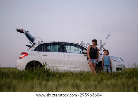 Mom with his Cute Little Boy Leaning their Back Against their Car with Problem While Waiting for Someone to Fix. - stock photo