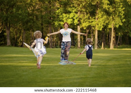 Mom with kids playing in the park. Children run to meet mom