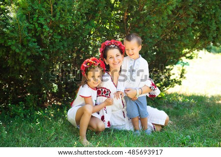 Mom with kids sitting near the tree dressed in Ukrainian national costume