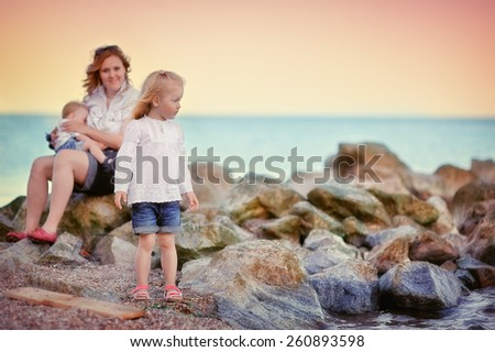 Mom with son and daughter resting on the shores of the sea - stock photo
