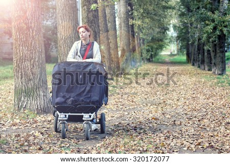 Mom with stroller walks in autumn park alley