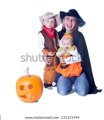 Mom with two kids in costume and pumpkin with a carved mug - stock photo