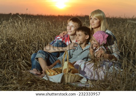 Mom with with her children on wheat field at a picnic