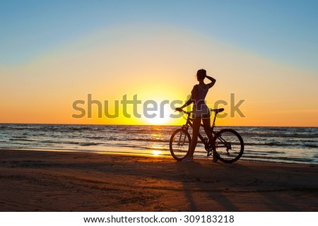 Moment in time. Young sporty woman cyclist silhouette contemplating the sunset on blue sky background on the beach. Summertime multicolored outdoors horizontal image. - stock photo