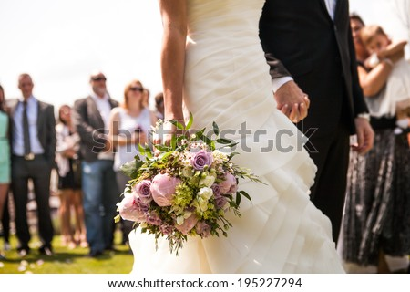 Moment in wedding,  bride and bridegroom holding hands with bouquet and wedding guests in background - stock photo