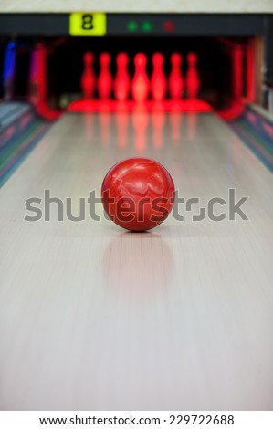 Moment when the heart stops beating. Close-up of bright red bowling ball rolling along bowling alley   - stock photo