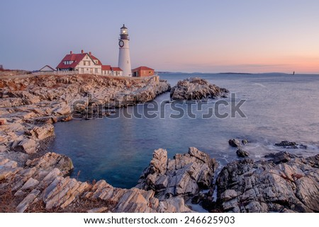 Moments before the sun rises a soft pink light is cast across the Portland Head Lighthouse and the rocks