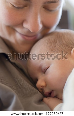 Moments of harmony and tenderness: Happy smiling mother holding her peaceful baby boy while he's sleeping on her chest.