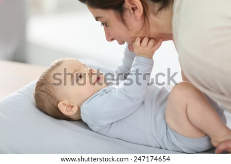 Mommy cuddling baby boy on changing table
