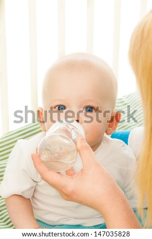 Mommy feeding little baby from bottle in his crib